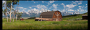 A panoramic image of one of the historic old barns in Grand Teton National Park with the Teton mountain range in the distance.