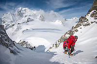 A pair of moutnaineers as seen venturing up snowy couloir of Aiguilles Marbrées with a clear view on Mont Blanc in the background.