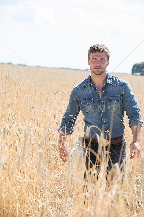 cowboy holding his hat while walking through a field