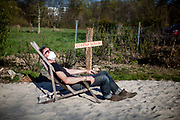 "Portrait of a man with a mask sitting on a beach chair on a place called ""Corona beach"" in times of social distancing related to the spreading of the corona virus."