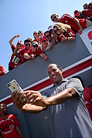 Men's basketball head coach Kevin Keatts uses a fan's iPhone to take a group selfie from the sidelines.