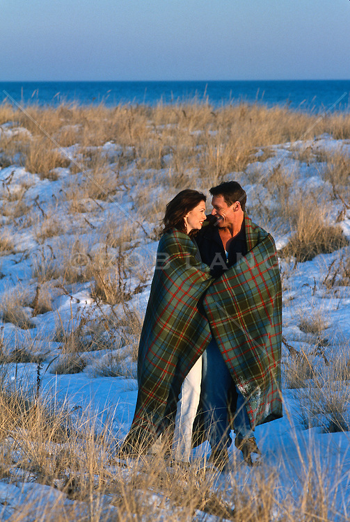 couple wrapped in a blanket walking  through snow covered beach in East Hampton, NY