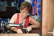 "Mar 23, 2009 -- BANGKOK, THAILAND: A seamstress works in her home in Ban Krua. The Ban Krua neighborhood of Bangkok is the oldest Muslim community in Bangkok. Ban Krua was originally settled by Cham Muslims from Cambodia and Vietnam who fought on the side of the Thai King Rama I. They were given a royal grant of land east of what was then the Thai capitol at the end of the 18th century in return for their military service. The Cham Muslims were originally weavers and what is known as ""Thai Silk"" was developed by the people in Ban Krua. Several families in the neighborhood still weave in their homes.     Photo by Jack Kurtz"
