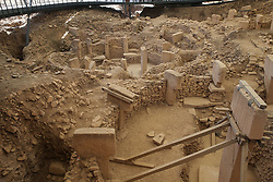 General view of Gobekli Tepe archaeological site in Sanliurfa, Turkey, on July 27, 2019. Gobekli Tepe is the oldest, biggest, and most mysterious archaeological site on the planet. Gobekli Tepe is the oldest megalithic structure ever found on earth. Discovered in modern-day Turkey, and still yet to be fully excavated, it dates to a baffling 12,000 years old. It's not just the oldest site; it's also the largest. Situated on a flat, barren plateau, the site is a spectacular 90,000 square meters. That's bigger than 12 football fields. It's 50 times larger than Stonehenge, and in the same breath, 6000 years older. The mysterious people who built Göbekli Tepe not only went to extraordinary lengths they did it with laser-like skill. Then, they purposely buried it and left. The site is located close to the Syrian border, in the Southeastern Anatolia Region of Turkey, about 12 km (7 mi) northeast of the city of Şanlıurfa. Göbekli Tepe means in English, Pot-Belly Hill. The tell has a height of 15 m (49 ft) and is about 300 m (980 ft) in diameter. It is approximately 760 m (2,490 ft) above sea level. The tell includes two phases of use, believed to be of a social or ritual nature by site discoverer and excavator Klaus Schmidt, dating back to the 10th–8th millennium BCE.[4] During the first phase, belonging to the Pre-Pottery Neolithic A (PPNA), circles of massive T-shaped stone pillars were erected – the world's oldest known megaliths. More than 200 pillars in about 20 circles are currently known through geophysical surveys. Each pillar has a height of up to 6 m (20 ft) and weighs up to 10 tons. They are fitted into sockets that were hewn out of the bedrock. In the second phase, belonging to the Pre-Pottery Neolithic B (PPNB), the erected pillars are smaller and stood in rectangular rooms with floors of polished lime. The site was abandoned after the Pre-Pottery Neolithic B (PPNB). Younger structures date to classical times. The details of the structure's functi