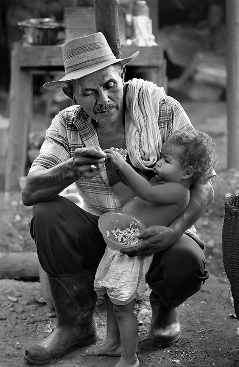 Pedro, a displaced man, feeds his grandchild in Pavarandó, a village which serves as a temporary refuge for hundreds of displaced families forced to flee their lands by a joint paramilitary & Colombian military offensive called ¨Operation Genesis¨.