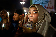 "A young Egyptian woman carries a vigil candle in a ceremony honoring  the ""shaheed,"" or martyrs—those Egyptians who died during protests in Tahrir Square, Cairo. More than three hundred Egyptians perished in protests across the country calling for the ouster of President Hosni Mubarak since January 25, 2011."
