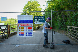 © Licensed to London News Pictures. 01/06/2020. LONDON, UK.  A workman closes a gate to the beach at Ruislip Lido in north west London.  Hillingdon Council has closed the beach to the public following several days where the public were not adhering to social distancing as coronavirus pandemic lockdown restrictions have been eased by the UK government.  On the first day of the meteorological summer, visitors who travelled from out of the area resorted to finding a place to sunbathe on any patch of grass they could find.  Photo credit: Stephen Chung/LNP