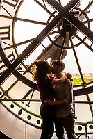 "Lovers embrace in front of the clock at Musee d""Orsay,  a museum in Paris, France, on the Left Bank of the Seine. It is housed in the former Gare d'Orsay, a Beaux-Arts railway station built between 1898 and 1900."