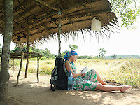 Young woman wearing dress sitting in shade of hut roof