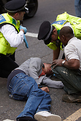 © licensed to London News Pictures. LONDON, UK  06/05/2011. An English Defence League (EDL) supporter lies injured on the road. Muslims against Crusades (MAC), founded by Anjem Choudary, are holding a prayer vigil for Osama Bin Laden outside the Us embassy in London. Please see special instructions for usage rates. Photo credit should read CLIFF HIDE/LNP