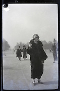 female person in fur coat walking in public park early 1900s Paris