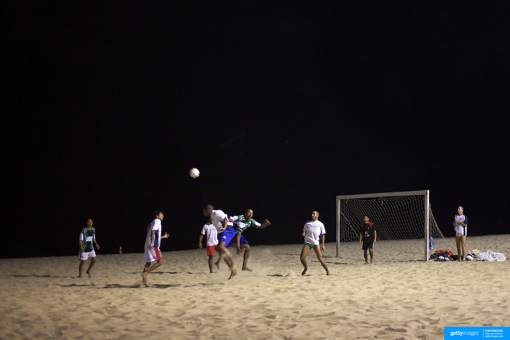 Locals play football at night time under floodlight on the beach at Ipanema beach, Rio de Janeiro, Brazil. 10th July 2010. Photo Tim Clayton..
