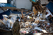 A Japan Self Defense Force member looks on as a fork lift truck clears debris from the streets in Tona, Miyagi Prefecture, Japan on  25 March 20011. .Photographer: Robert Gilhooly