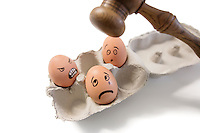 Funny faces on egg with gavel about to hit