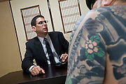 "Jake Adelstein, a former reporter at Japan's largest daily newspaper, Yomiuri Shimbun, author of ""Tokyo Vice"" speaks with his bodyguard, a former yakuza mobster who goes by the name ""Mochizuki,"" at an undisclosed location in Japan on Aug. 29, 2008. In 2005 American Adelstein uncovered a scandal involving senior members of Japan's mafia, the yakuza, visiting a medical center in Los Angeles to undergo liver transplants, despite being bared from entry due to having criminal records or suspected affiliation with Japanese organized crime groups. Within days, however, Adelstein was visited by mob members and told to either ""erase the story or be erased."" He took the former option and resigned from the Yomiuri, though a recent leak of his story has pushed Adelstein and his family into hiding..Photographer: Robert Gilhooly"