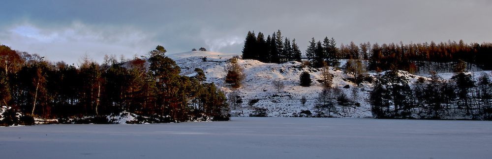 A frozen Tarn Howes lake, with the sun hitting the hills behind.