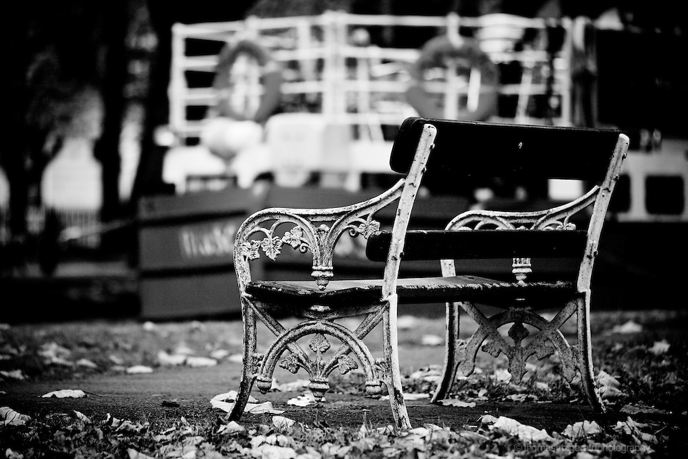 Dublin City, Ireland: An old iron and wooden bench stands on a leaf covered walk way by one of the two canals that passes through the centre of Ireland's capital. In the background a barge rests on the canals waters on this moody and dark autumn day.