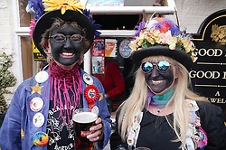 Portrait of two Morris dancers wearing costumes and makeup standing outside village pub smiling,