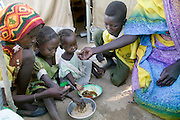 (MODEL RELEASED IMAGE). Squatting outside her UNHCR donated tent with her children, Sudanese Refugee D'jimia Ishakh Souleymane serves a pot of aiysh, the thick porridge that this refugee family eats three times a day. Despite losing almost everything in their flight from militia attacks, D'jimia keeps her improvised household as orderly as possible. To cover the ground inside, the family hauled in clean sand from the dry riverbed. D'jimia and the children sleep on two blankets, which she constantly airs out and washes. (Supporting image from the project Hungry Planet: What the World Eats.)