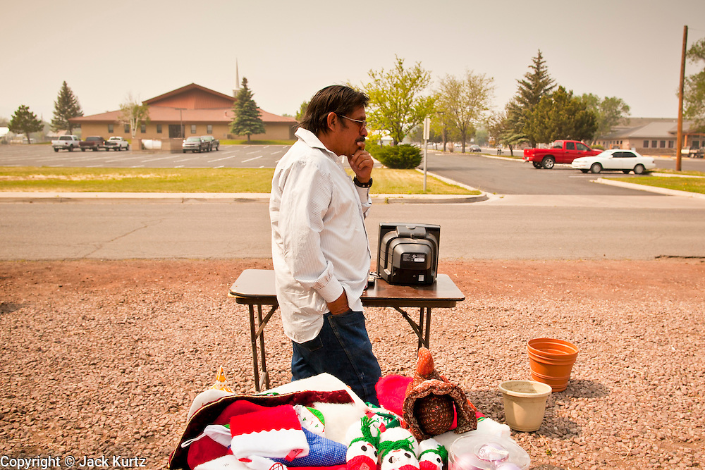 "03 JUNE 2011 - SPRINGERVILLE, AZ: Smoke fills the air while Jake Gomez (CQ) from Eager, looks at stuff for sale at a yard sale in Eager Friday. Gomez said he was concerned that the Wallow Fire might reach Eager. He said his home is surrounded by pinon juniper and cedar and they burn hot.  High winds and temperatures have continued to complicate firefighters' efforts to get the Wallow fire under control. The  mandatory evacuation order for Alpine was extended to Nutrioso, about 10 miles north of Alpine and early Friday morning fire was reported on the south side of Nutrioso. The fire grew to more than 106,000 acres early Friday with zero containment. A ""Type I"" incident command team has been called in to manage the fire.  PHOTO BY JACK KURTZ"