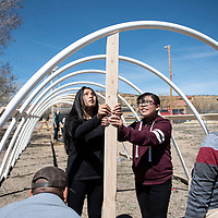 Dibe Yazhi Habitiin Community School seventh grade students Reneva Yazzie, left, and KayDence Low Dog, right, help build a door frame on one end of the hoop house, Thursday, March 28 in Crownpoint.