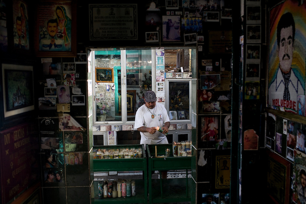 A man lights a candle in a chapel devoted to Jesus Malberde in Culiacan, Mexico.  Malverde is a folk saint worshipped by many people in the underworld and often associated with narcoculture and drug dealers. He is thought of as the Mexican version of Robin Hood, looking after those who have been forgotten by the Church and are involved in a life of crime.  People come to the chapel to show their respect and pray.