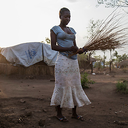 Early in the morning, Viola, 16, cleans the area around her tent at the Bidi Bidi refugee settlement in north Uganda on April 15, 2017.<br />