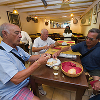 "VENICE, ITALY - JUNE 17: Three customers enjoy their cicchetti and wine at ""Ai Osti"" on June 17, 2011 in Venice, Italy. The bacari are the local down to earth version of wine bars, they serve  ""cicheti"" a sort of Tapas, traditionally washed down with a glass of wine, and Venetians stop to snack and socialize before and after meals."