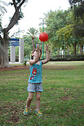 Preschool child of 5 plays ball in the park