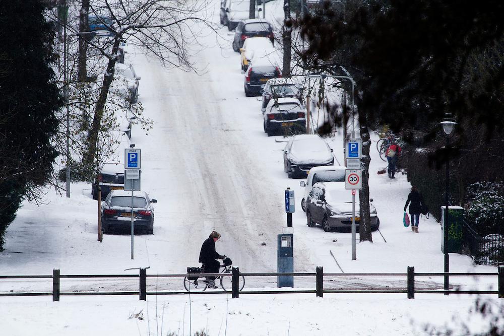 Een fietser rijdt op de Zijpendaalseweg in Arnhem langs een besneeuwde Van Pallantstraat.<br /> <br /> A cyclist is passing the snowy Van Pallandstraat in Arnhem.