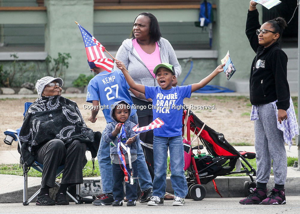Spectators  wave U.S. flag as the Martin Luther King Jr. parade makes it's way down Martin Luther King Blvd. in Los Angeles on Monday Jan. 18, 2016. The 31st annual Kingdom Day Parade honoring Martin Luther King Jr. was themed &quot;Our Work Is Not Yet Done&quot;(Photo by Ringo Chiu/PHOTOFORMULA.com)<br /> <br /> Usage Notes: This content is intended for editorial use only. For other uses, additional clearances may be required.