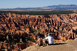 Couple relaxing at Bryce Canyon National Park, Ampitheater and Hoodoos of Silent City from Bryce Point, dawn, erosion, arid, Utah, UT, Southwest America, American Southwest, US, United States, tourists, travelers, sightseeing, no model release, Image ut341-17541, Photo copyright: Lee Foster, www.fostertravel.com, lee@fostertravel.com, 510-549-2202