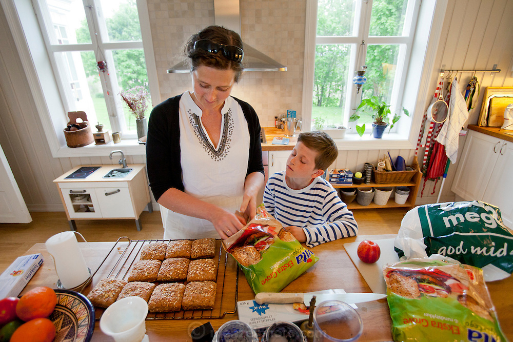 Anne Glad Fredricksen, 45, with her son, Amund, 8, as she prepares the evening meal after work in their farmhouse kitchen. Model Released.