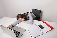 Exhausted businesswoman sleeping at office desk
