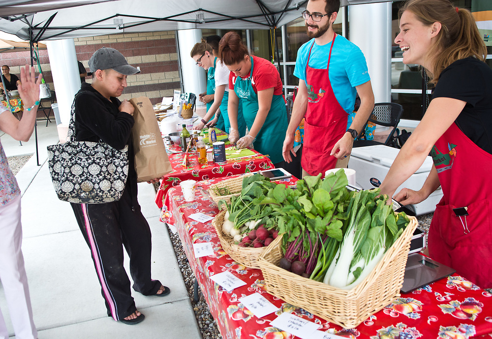 Natalie Donnelly, front right, community food projects coordinator with Presbyteriean Center for Community Health chats with customers after Melissa Lucero, left, purchased a bag of fresh produce from the Mobile Farmers' Market, Tuesday, June 6, 2017. The market made three stops, including one outside of First Choice Community Healthcare at 2001 El Centro Familiar Blvd. SW.  (Marla Brose/Albuquerque Journal)