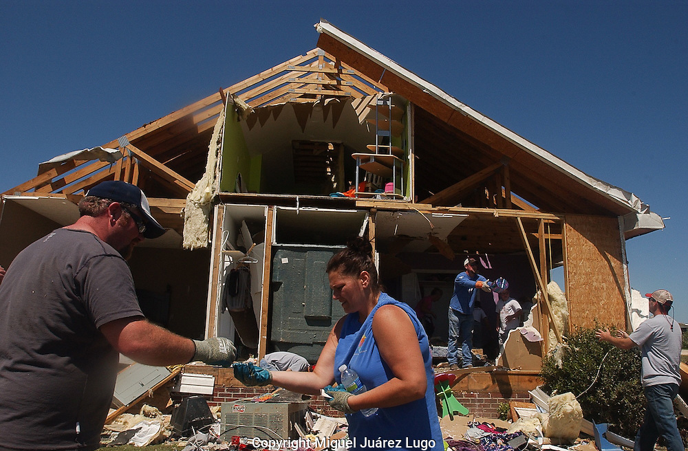 "Rainville, Alabama: Jason Sarratt hands his wife, Melanie, a set of keys he found in the debris of their ruined house. At least seven houses in their subdivision--knicknamed ""Rainbow's End""--where obliterated when one of many tornadoes swept through the area Wednesday. At least 32 people are confirmed dead in Dekalb County in northeastern Alabama. (PHOTO: MIGUEL JUAREZ LUGO)"