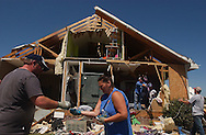 """Rainville, Alabama: Jason Sarratt hands his wife, Melanie, a set of keys he found in the debris of their ruined house. At least seven houses in their subdivision--knicknamed """"Rainbow's End""""--where obliterated when one of many tornadoes swept through the area Wednesday. At least 32 people are confirmed dead in Dekalb County in northeastern Alabama. (PHOTO: MIGUEL JUAREZ LUGO)"""