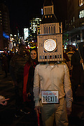 "New York, NY - 31 October 2016. A man in the annual Greenwich Village Halloween Parade wears a costume that includes the iconic clock tower of the British Parliament and a sign that reads ""Help me I'm Brexit."""