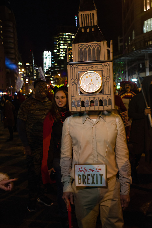 """New York, NY - 31 October 2016. A man in the annual Greenwich Village Halloween Parade wears a costume that includes the iconic clock tower of the British Parliament and a sign that reads """"Help me I'm Brexit."""""""