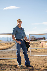 hot blond cowboy leaning against a gate on a ranch