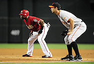 Apr. 17 2011; Phoenix, AZ, USA; Arizona Diamondbacks Justin Upton (10) leads off first base ahead of first basemen .Brandon Belt (9) during the first inning against the San Francisco Giants at Chase Field. Mandatory Credit: Jennifer Stewart-US PRESSWIRE.