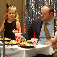 Matt Blanchard of Guntown, holds his youngest daughter Liza Kate, 1, as he eats with his other two daughters Livie, 3, and Ella, 7, not pictured, as they attend the Daddy Daughter Dinner at Chick-fil-a Tuesday night in Tupelo.