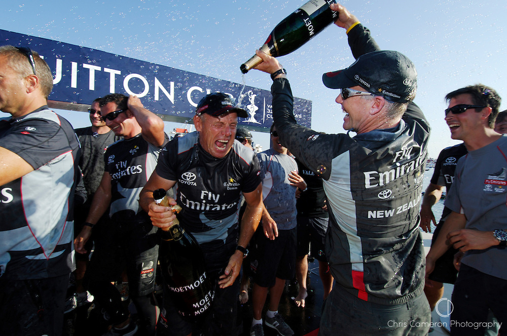 Emirates Team New Zealand tactician Terry Hutchinson empties a bottle of Moet over Grant Dalton. Louis Vuitton Cup presentation ceremony. 6/6/2007