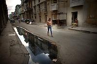 Woman walking down street in Havana, Cuba.