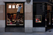 In a scene of rectangles, a shop worker balances while adjusting a new window display in a store, on 9th December 2016, in the City of London.