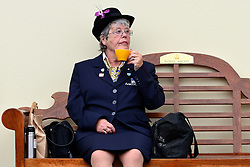 © London News Pictures. 20/06/2013. Ascot, UK. A woman rests on a bench and has a cup of tea from her flask. Ladies Day on day three of Royal Ascot at Ascot racecourse in Berkshire, on June 20, 2013. The 5 day showcase event, which is one of the highlights of the racing calendar, has been held at the famous Berkshire course since 1711 and tradition is a hallmark of the meeting. Top hats and tails remain compulsory in parts of the course.  Photo credit : Stephen Simpson/LNP
