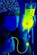 A doctor with a skull head wrap hold an IV with a poisonous fluid.Black light