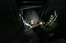 ©Licensed to London News Pictures. 27/12/2011. Gaza. .A man stands next to the body of a Palestinian who was killed after a reported Israeli air strike in the northern Gaza Strip December 27, 2011. Photo Credit: Yasser Fathi /PNC/LNP