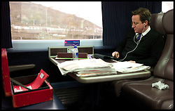 """File Photo - Prime Minister David Cameron leaves official red box behind on train.<br /> The Prime Minister David Cameron working on the train on the way to Swansea, Wales, to deliver a speech, Friday April 1, 2011. Photo By Andrew Parsons/ i-Images.<br /> <br /> <br /> The Prime Minister who was going to a wedding near York got the 7.44am train at King's Cross on Saturday 7th September 2013. The PM departed the train, leaving the red box behind with the key still in it and no security within touching distance. A No10 spokesman said last night: 'The box was not left unattended.<br /> """"The Prime Minister's security detail was there at all times.""""<br /> Monday 9th September, 2013. Photo By Andrew Parsons / i-Images"""