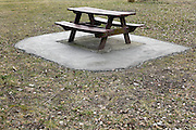 picnic bench in a public park placed on a large concrete flooring